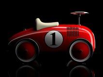 Rétro voiture rouge numéro un de jouet d'isolement sur le fond noir Photographie stock
