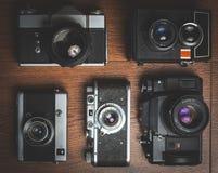 Rétros appareils-photo aléatoires sur la table en bois Images stock