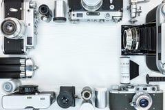 Rétros appareils-photo de photo de vintage, petits pains de film, lentille, trépieds sur le blanc images stock