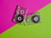 Rétros cassettes démodées sur un fond au néon vert rose Vue supérieure Images libres de droits