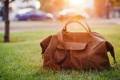 Rétros chaussures brunes et sac en cuir d'homme dans l'herbe colorée lumineuse d'été en parc Photos stock