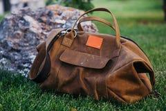 Rétros chaussures brunes et sac en cuir d'homme dans l'herbe colorée lumineuse d'été en parc Photo libre de droits