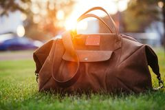 Rétros chaussures brunes et sac en cuir d'homme dans l'herbe colorée lumineuse d'été en parc Images libres de droits