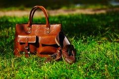 Rétros chaussures brunes et sac en cuir d'homme dans l'herbe colorée lumineuse d'été Photos stock