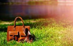 Rétros chaussures brunes et sac en cuir d'homme dans l'herbe colorée lumineuse d'été Photographie stock