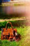 Rétros chaussures brunes et sac en cuir d'homme dans l'herbe colorée lumineuse d'été Photo libre de droits