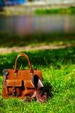 Rétros chaussures brunes et sac en cuir d'homme dans l'herbe colorée lumineuse d'été Image stock