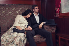 Rétros couples dans la voiture de train de vintage Image stock