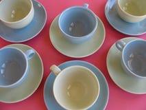 Rétros ensembles colorés de tasse et soucoupe sur le fond rose Photographie stock