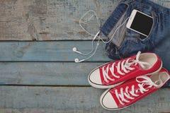Rétros espadrilles et smartphone rouges avec des casque-écouteurs dans un PO Image libre de droits