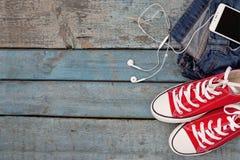 Rétros espadrilles et smartphone rouges avec des casque-écouteurs dans un PO Photographie stock libre de droits