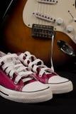 Rétros espadrilles rouges et guitare brouillée à l'arrière-plan Image libre de droits