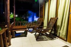 Rétros meubles en bois Vieilles table et chaises en bois, support sur le porche d'une maison de pavillon Sur la rue la nuit photos stock