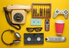 Rétros objets sur un fond jaune Téléphone rotatoire, cassette sonore, cassette vidéo, gamepad, 3d verres, extérieur de TV photo stock