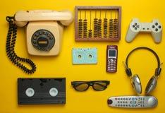 Rétros objets sur un fond jaune Téléphone rotatoire, cassette sonore, cassette vidéo, gamepad, 3d verres, extérieur de TV image libre de droits