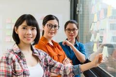 Réunion assez femelle d'équipe d'affaires sur le mur de verre Images libres de droits