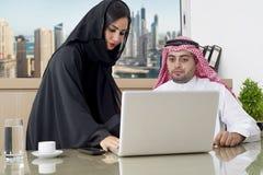 Réunion d'affaires dans le bureau, l'homme d'affaires Arabe et le hijab de port de secrétaire Arabe travaillant sur l'ordinateur  Photos libres de droits