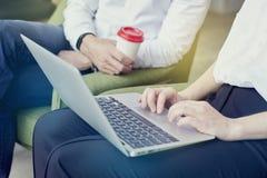 Réunion d'affaires dans le bureau moderne, utilisant l'ordinateur portable sur des genoux, entrepreneur travaillant ensemble sur  Photographie stock libre de droits
