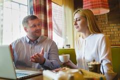 Réunion d'affaires dans un café homme heureux ou réussi et femme regardant le comprimé Image stock
