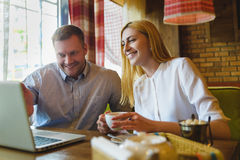 Réunion d'affaires dans un café homme heureux ou réussi et femme regardant le comprimé Images stock