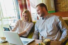 Réunion d'affaires dans un café homme heureux ou réussi et femme regardant le comprimé Photos libres de droits