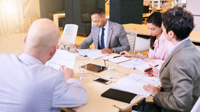 Réunion d'affaires entre quatre cadres entreprenants professionnels à l'intérieur Images libres de droits