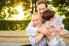 réunion de famille Un homme et un garçon sont venus pour voir leur grand-père qui s'assied en parc sur un fauteuil roulant Images libres de droits