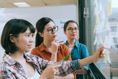 Réunion femelle d'équipe de concepteur sur le mur de verre Images libres de droits