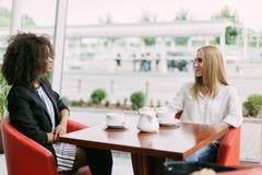 Réunion gaie de deux amis dans le café L'un d'entre eux est afro-américain Images libres de droits