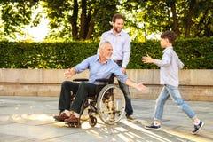 Réunion gentille Le fils et le petit-fils sont venus chez le vieil homme sur un fauteuil roulant Photo stock