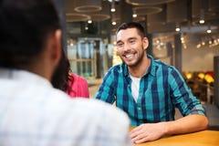 Réunion heureuse d'homme avec des amis au restaurant Photographie stock libre de droits