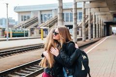 Réunion heureuse de deux amis étreignant dans la rue Photo stock