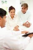Réunion indienne supérieure de couples avec le conseiller financier à la maison Image stock