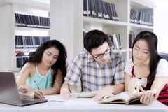Réunion internationale de groupe d'étudiants dans une bibliothèque Photo libre de droits