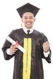 réussi du jeune homme d'obtention du diplôme souriant tout en tenant le diplôme Images libres de droits