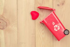 Réutilisez la poubelle avec le coeur sur le fond en bois Images stock