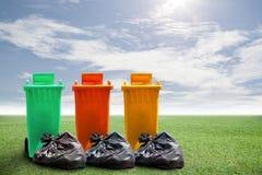Réutilisez les poubelles et les déchets de sac sur le fond d'herbe verte et de ciel, photo stock