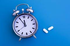 Réveil avec des pilules photographie stock