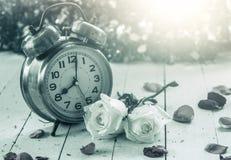 Réveil avec la rose de blanc sur le fond en bois Photographie stock libre de droits