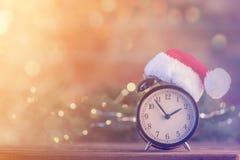 Réveil avec le chapeau de Santa Claus avec la fée Ligths de Noël Photographie stock libre de droits