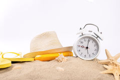 Réveil blanc de vintage avec des articles de plage sur le sable Image libre de droits