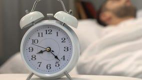Réveil blanc tenant le lit proche avec l'homme de sommeil, sommeil sain, plan rapproché banque de vidéos