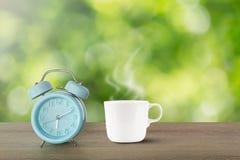 Réveil classique bleu et tasse de café blanc chaude avec la vapeur sur le bureau en bois de vintage sur le fond vert brouillé de  images stock