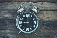 Réveil classique en métal brillant sur le backgro en bois très vieux de table Photographie stock libre de droits