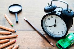 Réveil, crayon et crayons de couleur sur le bureau en bois, de nouveau au Sc Photo stock