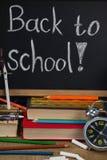 Réveil, crayons, craie, livres et ardoise avec de nouveau au texte d'école Image stock