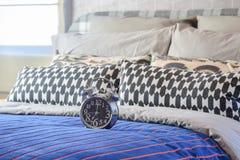 Réveil décoratif avec les oreillers noirs et blancs sur le lit image stock