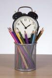 Réveil dans le récipient avec les crayons colorés Photographie stock