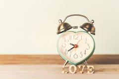 Réveil de coeur avec amour de mot d'amour sur la table Photographie stock libre de droits