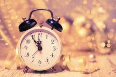 Réveil de vintage montrant cinq au minuit sur le scintillement abstrait Photo libre de droits